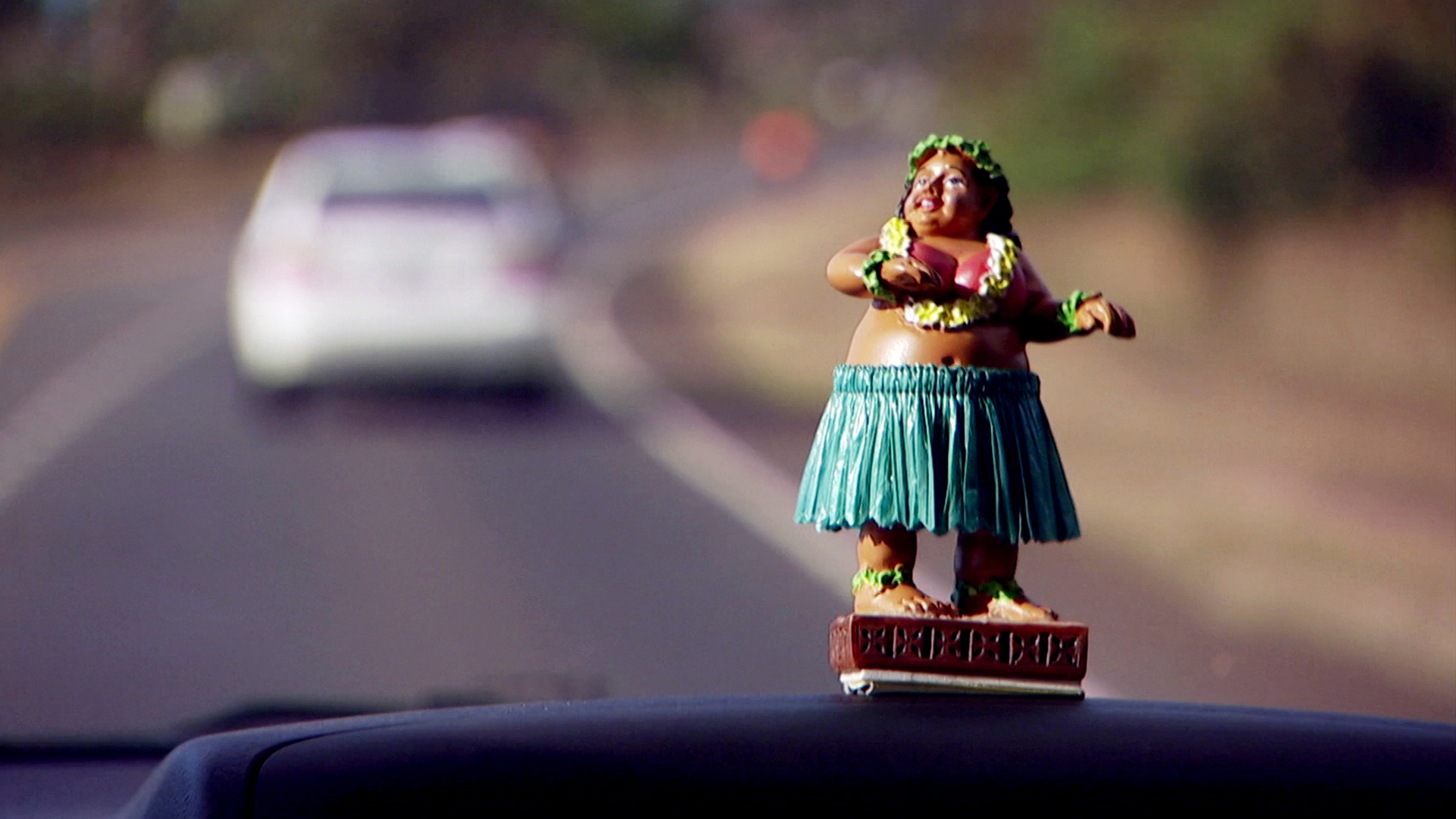 A dashboard hula dancer in the front of a moving car.